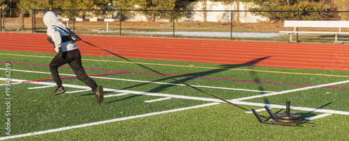 Fotomural Athlete pulling a weighted sled on a turf field