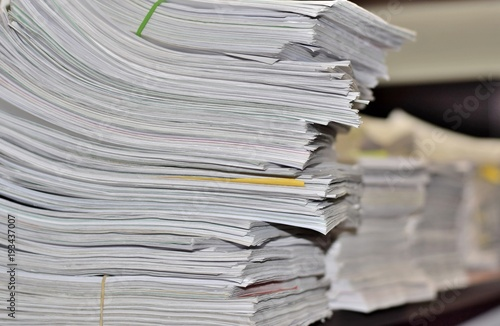 Fotografie, Obraz  Stacks of paperwork sitting on an office desk in a messy but organized fashion