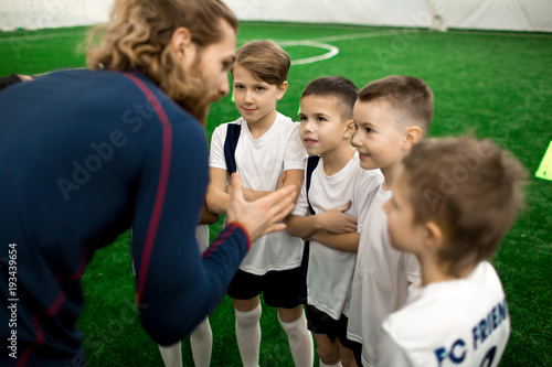 Young football trainer talking to team of little players on the field during bre Fototapete