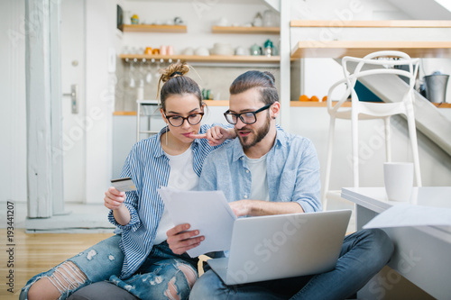 Fotografia, Obraz  Young couple paying bills with credit card