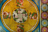 Asian women and myth animals on ceiling of ancient Buddhist temple with paintings