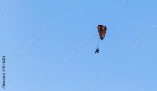 Paraglider flies in blue sky, ultralight aircraft