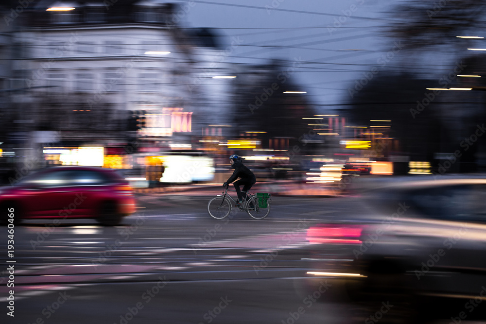 Fototapety, obrazy: A cyclist drives at twilight over a road intersection