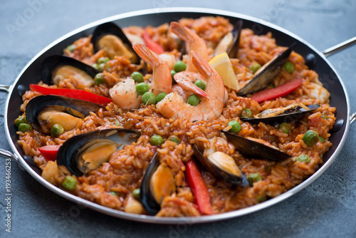 Spanish paella with seafood in a frying pan, selective focus, horizontal shot