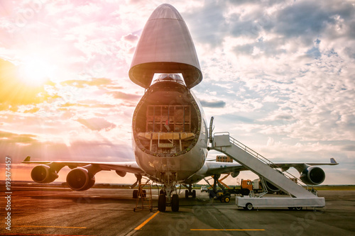 Obraz Unloading wide body transport cargo aircraft in the morning sun - fototapety do salonu