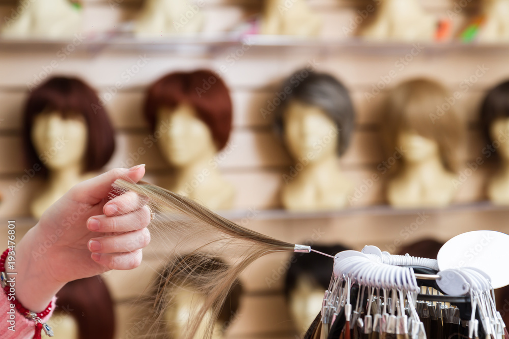 Fototapeta girl in her hand chooses a hair color wig of a natural blond. A palette of hues of hair color in a store of wigs on a blurry