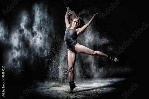 Slika na platnu Girl dansing with flour on black background