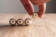 Hand Putting On Good Word Written In Wooden Cube