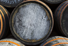 Stacked Pile Of Old Wooden Barrels And Casks At Whisky Distillery In Scotland