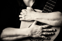 Hands Hugging An Acoustic Guitar