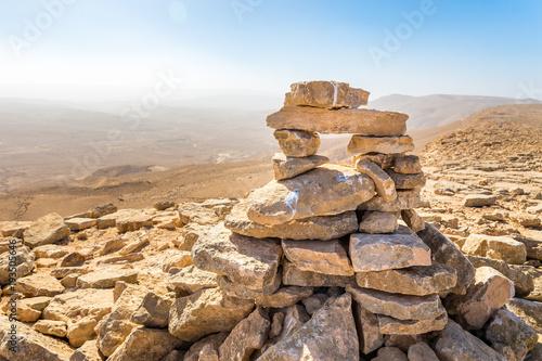 Stone cairn top mountain hiking trail sign, Israel desert. Fototapete