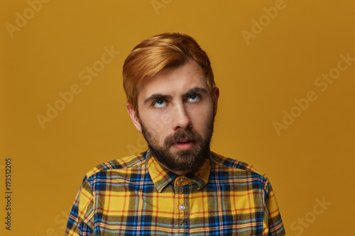 Fotografie, Obraz  Boring to death! Young bearded male, wearing yellow t-shirt, dyed hair feels bored and thinkin about home