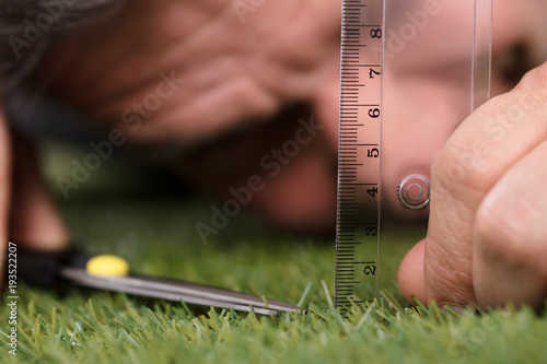 Valokuva Man Using Measuring Scale While Cutting Grass