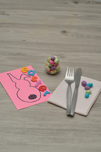 An Easter Place Setting With A Napkin, Knife, Fork And A Bowl Of Candy Displayed On A Table With An Easter Bunny Card