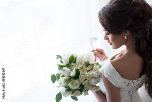Carta da parati attractive bride in traditional dress with wedding bouquet and glass of champagn
