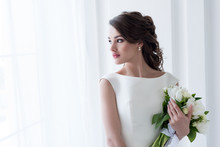 Beautiful Bride Holding Wedding Bouquet And Looking At Window