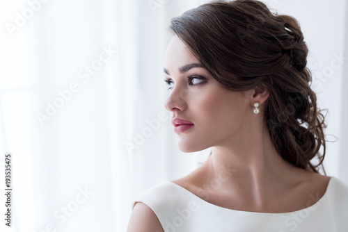 attractive brunette woman in white dress looking at window Fototapete