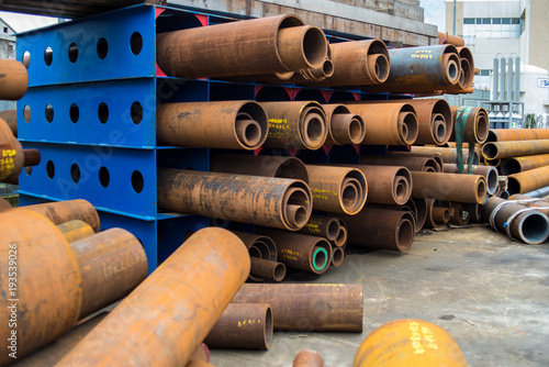 Rusty metal pipe sections stored in a blue pipe rack Fototapeta