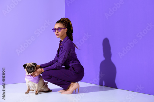Fototapeta attractive african american young woman posing in purple suit with pug, ultra violet trend obraz