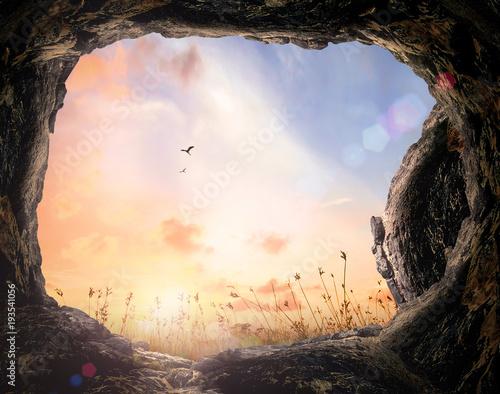 Carta da parati Resurrection of Easter Sunday concept: Tomb stone and meadow autumn sunrise back