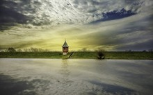 The Small Water Gaging House On Elbe River, Cloudy Sky Is Reflected In Water
