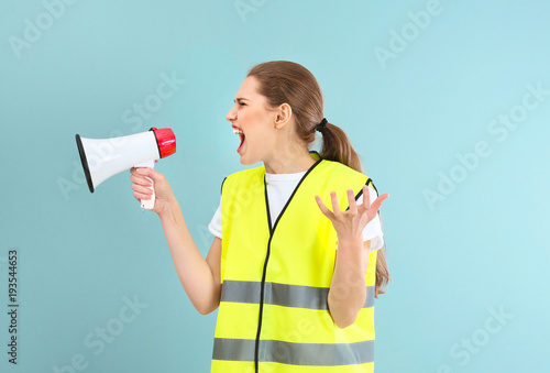 Fotografía  Young woman in reflective vest shouting into megaphone on color background