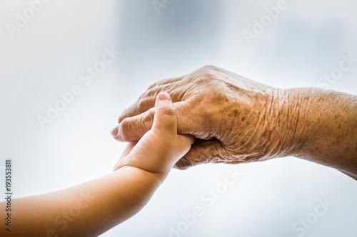Photo Kind und alte Frau halten die Hand