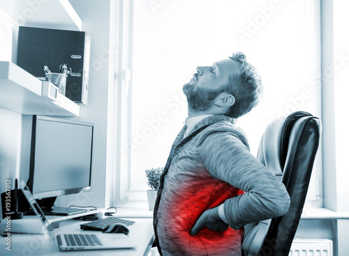 Man in office suffering from back pain, red dot around