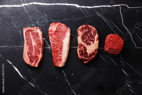 Spoed Foto op Canvas Vlees Variety of Raw Black Angus Prime meat steaks Blade on bone, Striploin, Rib eye, Tenderloin fillet mignon on dark marble background copy space