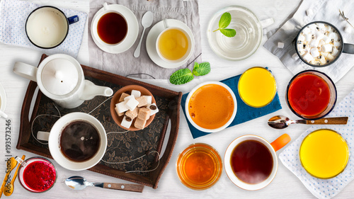 Spoed Foto op Canvas Thee Different cold and hot drinks on wooden table. Tea, milk, juice,coffee, smoothie, water, pot, tray and tissue. Concepts of healthy traditional tasty drinks.