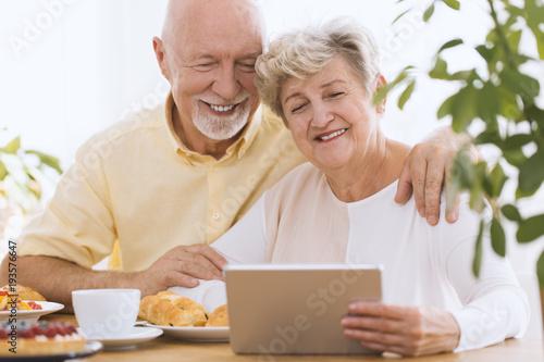 Lovely senior couple using tablet Poster