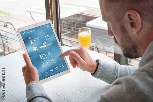 Smart home control app on laptop display in man hands.