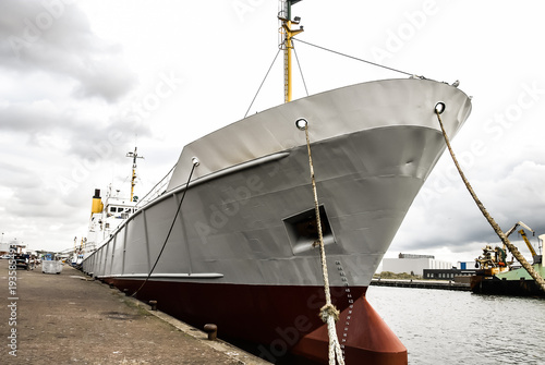 A front view of a large fishing vessel, standing in the dock of IJmuiden, the Netherlands.