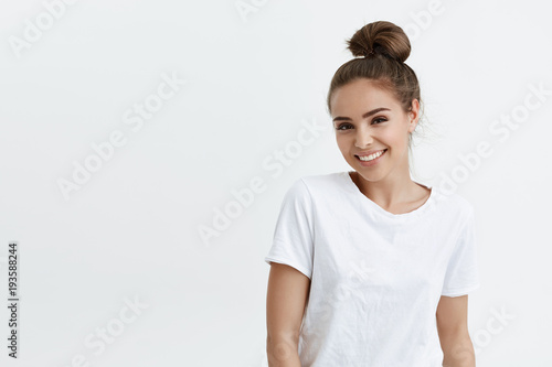 Charming adult caucasian woman with bun smiling broadly and glancing at camera, standing against white background. Cute wife on meeting with girlfriends. Girl in dressing room changes to her sportsuit