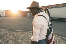 Young Man Wearing Hat And Sunglasses Holding American Flag