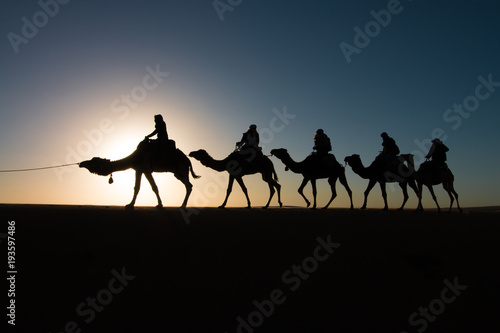 People on camels silhouettes in the sahara in Morocco Wallpaper Mural