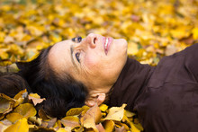 Portrait Of Smiling Middle Aged Woman Lying On The Ground Full Of Brown And Yellow Leaves In The Park During Fall Season. Pretty Mature Lady With Positive Expression, Dreaming Feeling, Visionary
