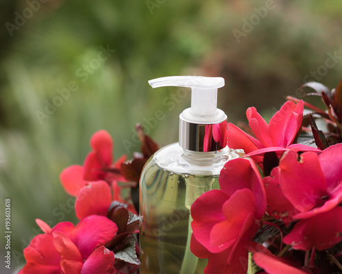 Dispenser bottle of green liquid soap or shampoo is among flowers red-pink color. Image is on a blurred background of garden greenery and has an effect of 3 ...