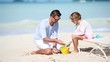 Father and little adorable girl making sand castle at tropical beach
