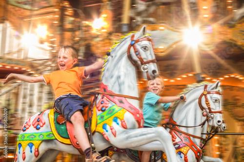Valokuva  begeisterte Kinder auf einem Karussell mit Pferden