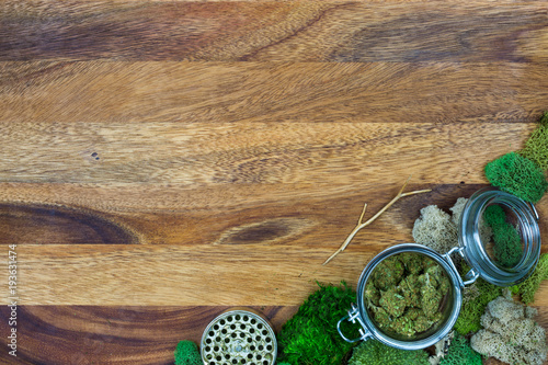 Photo  Marijuana in glass jar surrounded by moss and grinder with wooden background