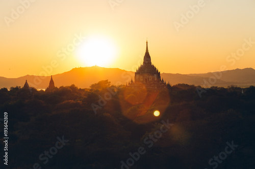 Photo  Bagan, Myanmar - FEB 21th 2014: Sunset landscape view with silhouettes of Buddhi