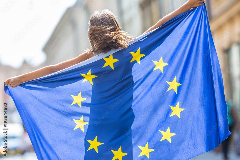 Fototapeta EU Flag. Cute happy girl with the flag of the European Union. Young teenage girl waving with the European Union flag in the city