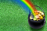 Fototapeta Tęcza - Saint Patrick's Day and Leprechaun's pot of gold coins concept with a rainbow indicating where the leprechaun hid treasure on green with copy space. St Patrick is the patron saint of Ireland