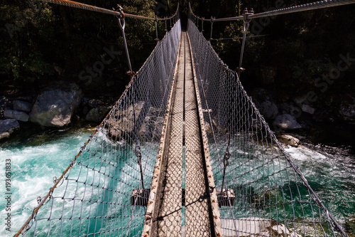 Fotografía  Suspension bridge over a beautiful turquoise river on the Hollyford Road, Fiordl