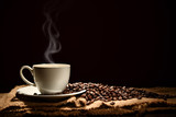Fototapeta Coffie - Cup of coffee with smoke and coffee beans on black background