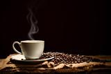 Fototapeta Kawa jest smaczna - Cup of coffee with smoke and coffee beans on black background