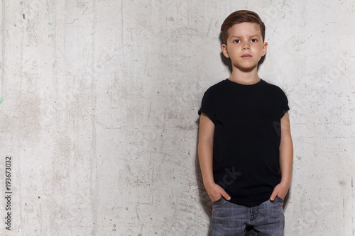Fototapeta Cute little boy in black T-shirt posing in front of grunge concrete wall. Portrait of fashionable male child, copy space. Boy looks at camera, gray wall on background. obraz