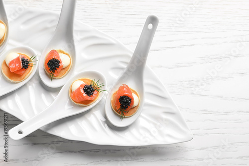 Foto op Aluminium Voorgerecht Tasty appetizers with black caviar and salmon in ceramic spoons on plate