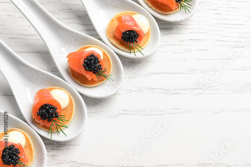 Foto op Plexiglas Voorgerecht Tasty appetizers with black caviar and salmon in ceramic spoons on table